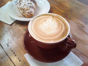 A latte and an Aalmond croissant from Four Barrel Caffee